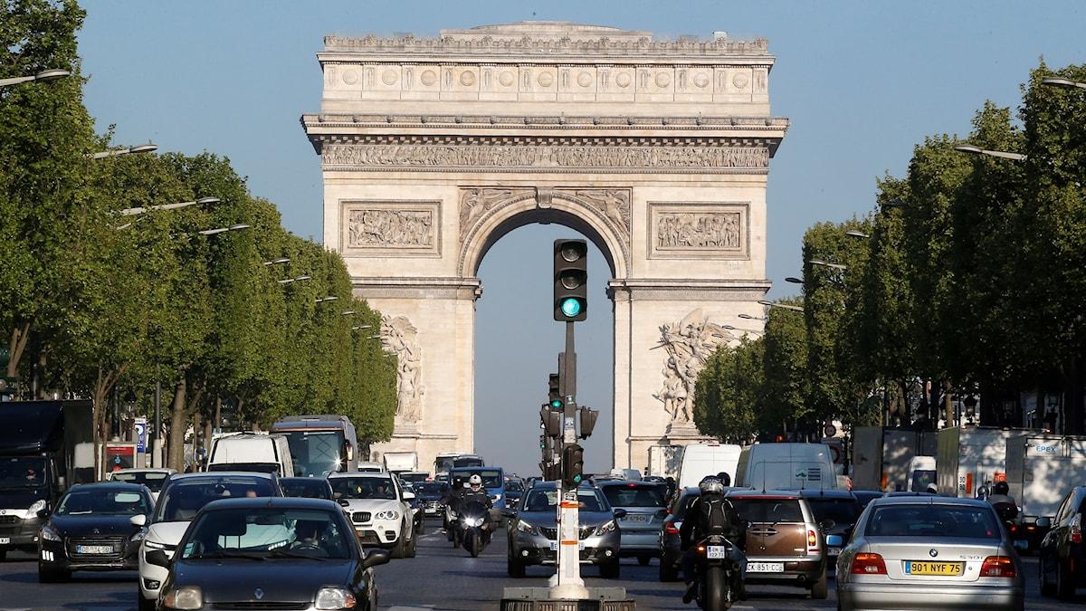 En trafikerad Champs-Élysées med Triumfbågen som syns längst bort.