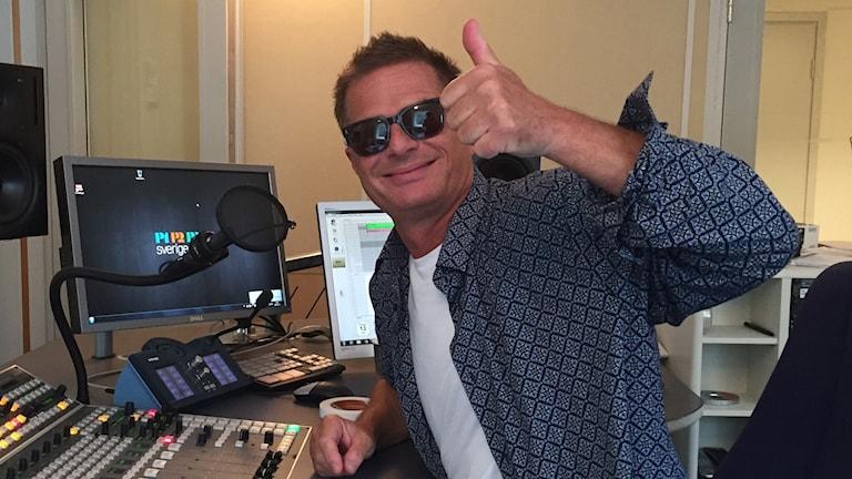 Man med solglasögon sitter vid ett mixerbord och ger tummen upp.
