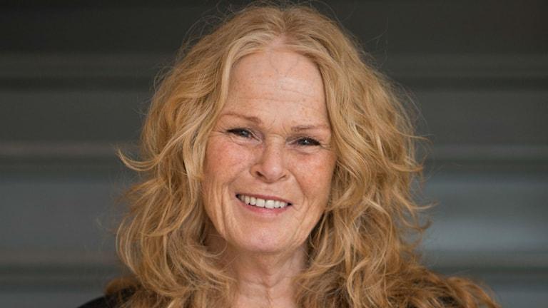 En leende Ulla-Maria Andersson med utsläppt axellångt lockigt hår.