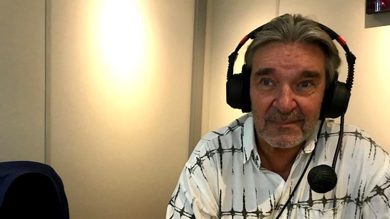 Vit man i 60-årsåldern i radiostudio, har på sig headset.