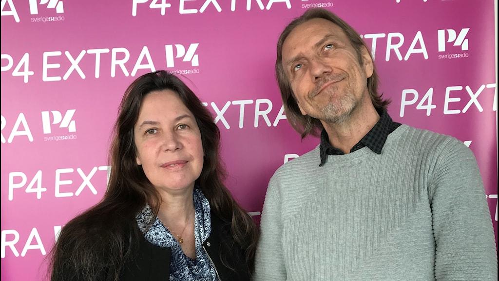 Kvinna och man ståendes framför rosa fotovägg