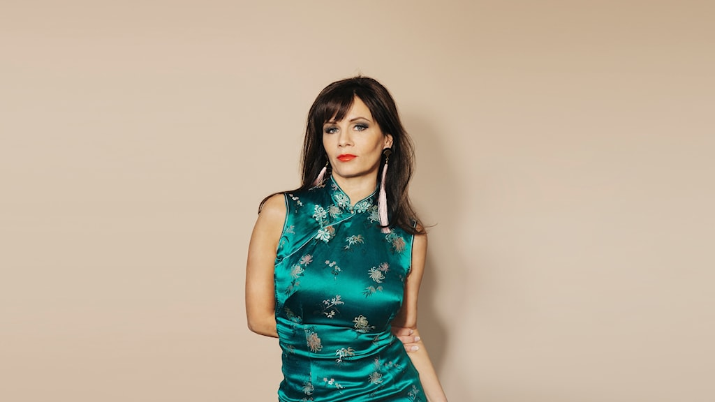 Lena Philipsson poserar i en turkos klänning.