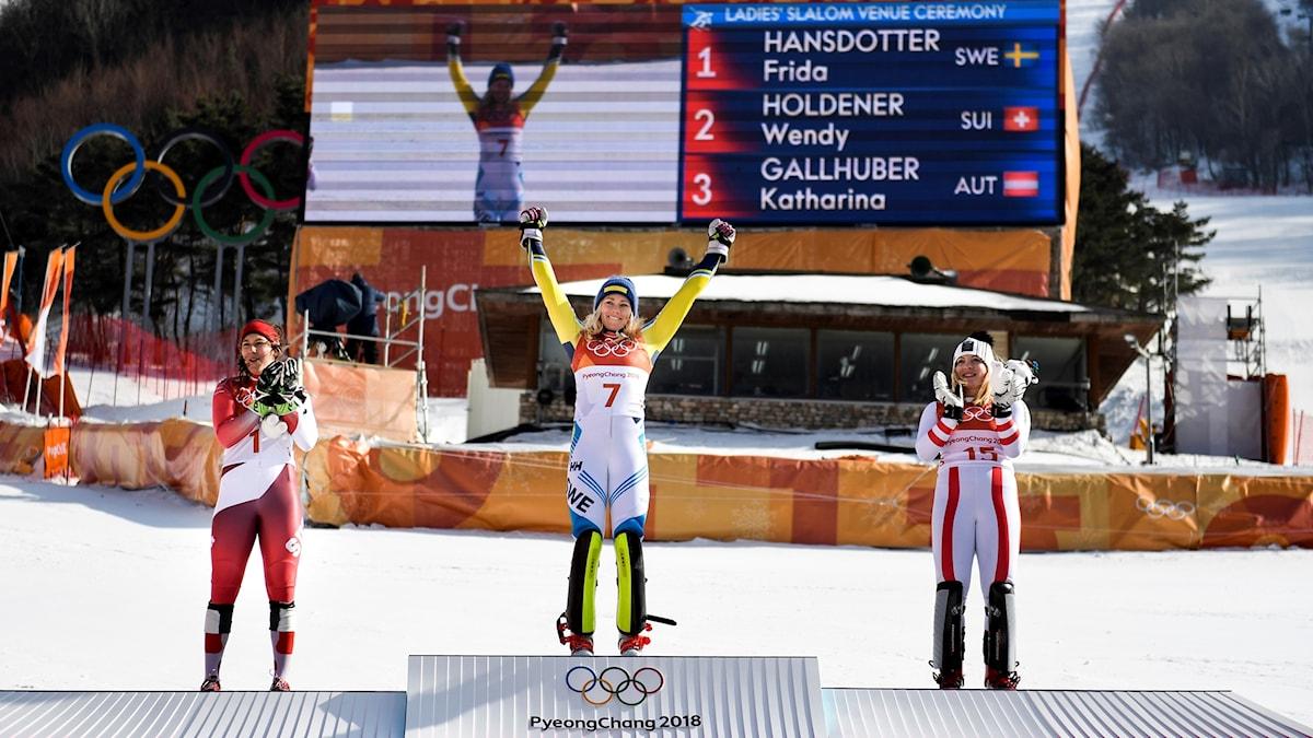 Frida Hansdotter högst upp på pallen före silver medaljör Wendy Holdener, SUI, och bronsmedaljör Katharina Gallhauber, AUT, efter att hon vunnit OS-guld i damernas slalom vid vinter-OS i Pyeongchang.