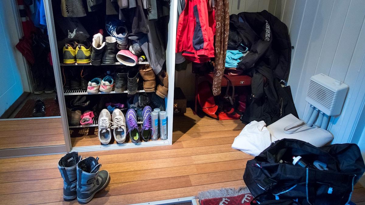Skor och jackor som trängs i en hall.