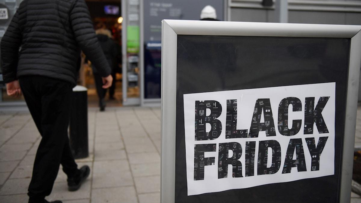 En man går in i en butik som skyltar med att det är Black monday.