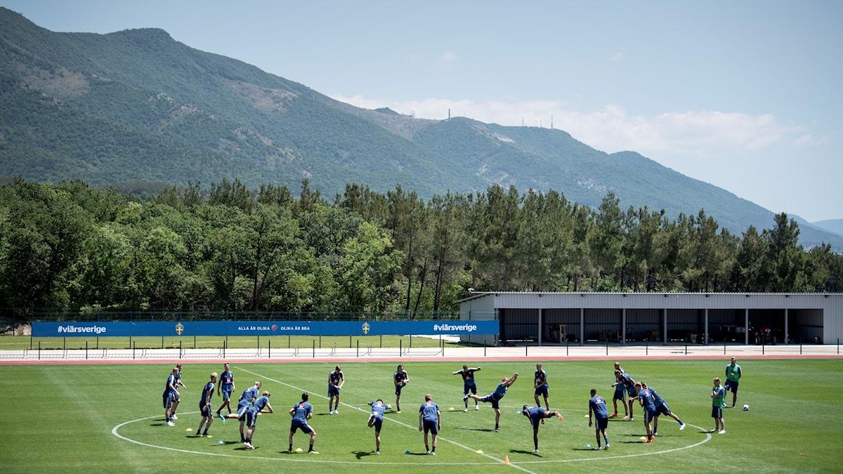 Fotbollslandslaget står i mitten av en träningsplan och stretchar.