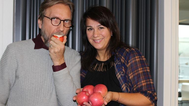Erik och Alexandra med äpplen i handen och i munnen.