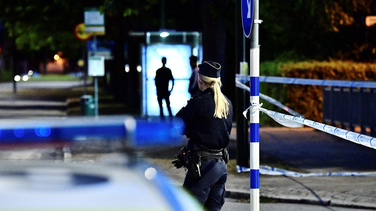 En polis står bakom en polisbild bredvid avspärrningar.