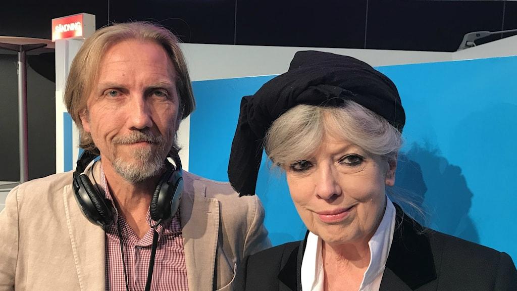 En vit man i 60-årsåldern med hörlurar klädd i kaval. Till höger, vit kvinna i 70-årsåldern med huvudbonad.