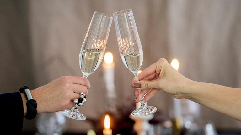 Närbild på två händer, skålar med champagneglas