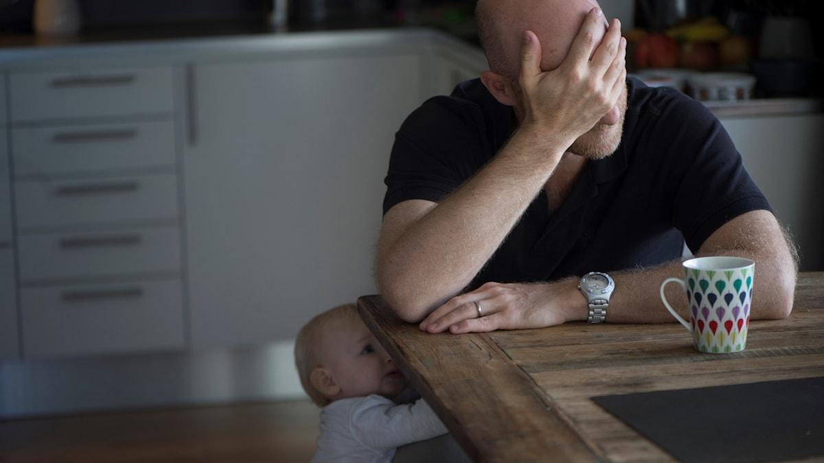 En deprimerad man sitter ensam hemma vid köksbordet med huvudet i händerna. Ett barn försöker få hans uppmärksamhet.