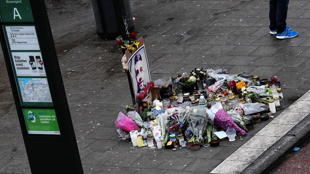 Blommor och ljus framför ett porträtt av den mördade 16-årige Ahmed Obaid på busshållplatsen på Amiralsgatan i Rosengård i Malmö.