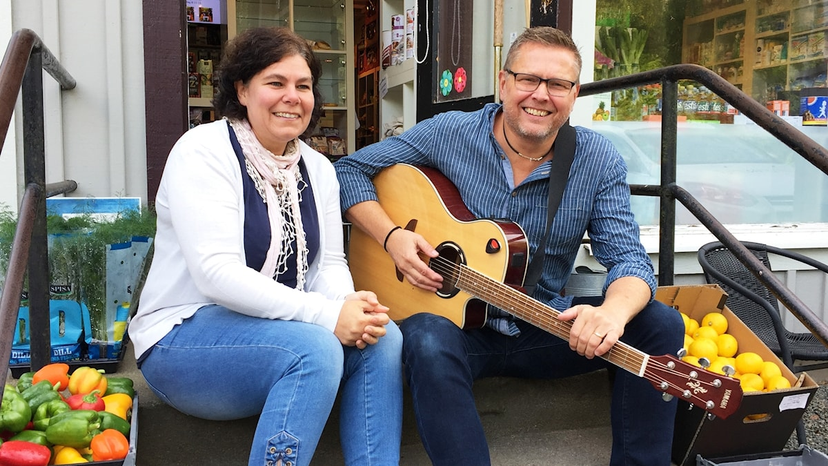 En kvinna och en man sitter på en trappa. Vid sidorna paprikor och citroner. Mannen har en gitarr i famnen.