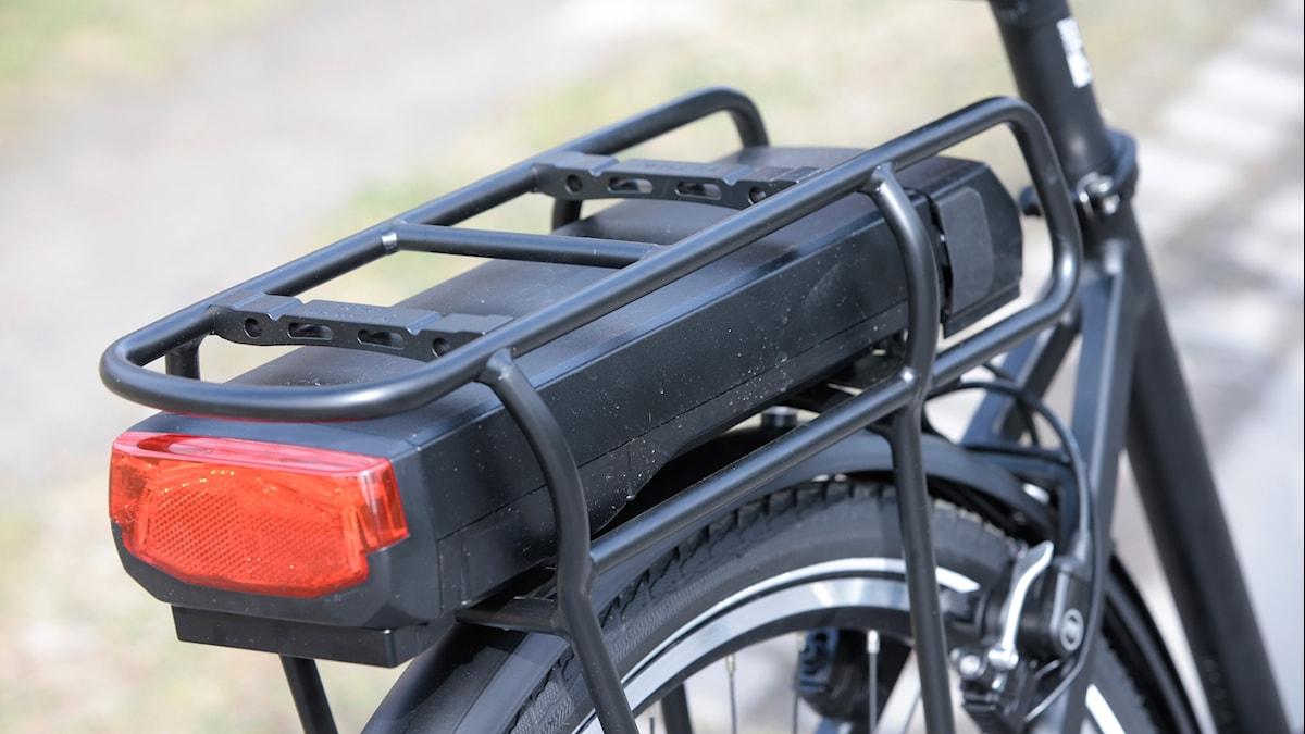 Pakethållaren på en elcykel där man ser att batteriet sitter.