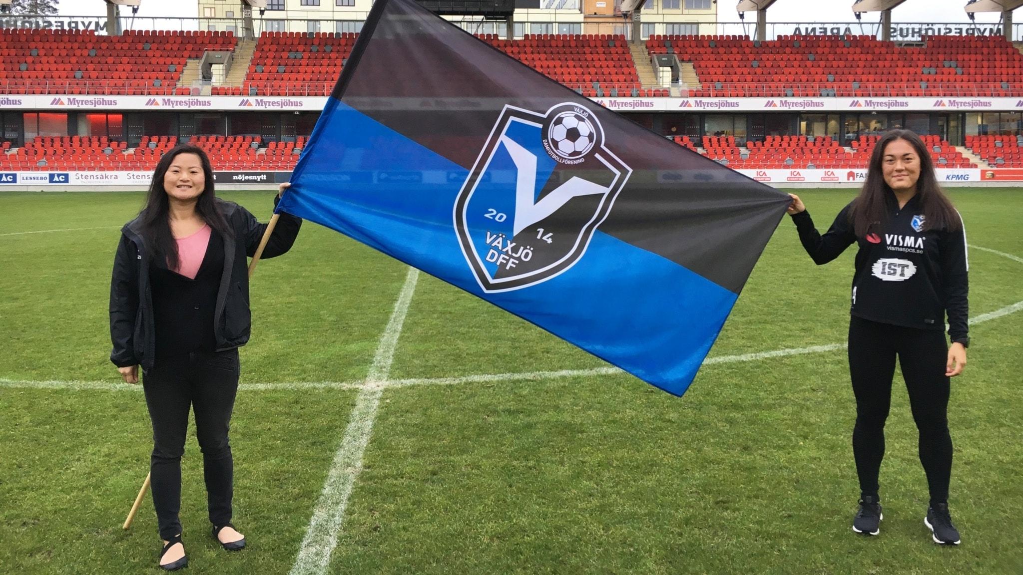 Två tjejer står på en fotbollsplan och håller upp Växjö DFF:s flagga.