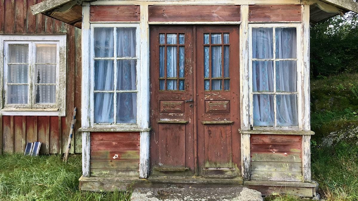 Ingången till Erik och Sigvards hus i Hågeryd, det är ett rött och vitt slitet hus, där färgerna knappt sitter kvar.