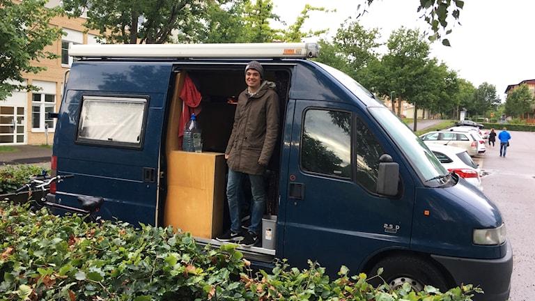 En kille står i jacka och mössa inne i en blå skåpbil.