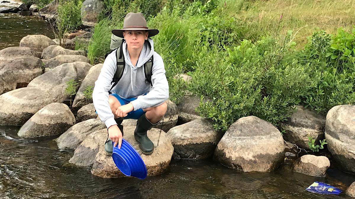 En kille med hatt sitter vid vattnet och vaskar guld.