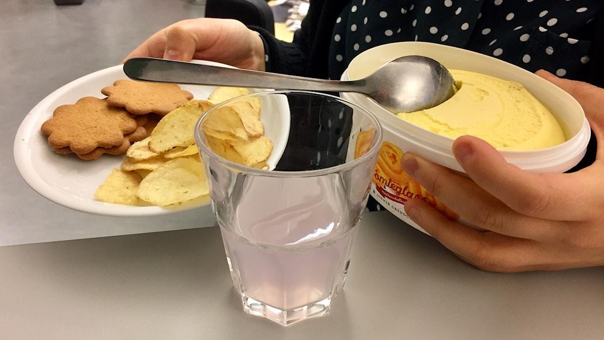 En tallrik hålls upp med pepparkakor och chips och ett glasspaket.