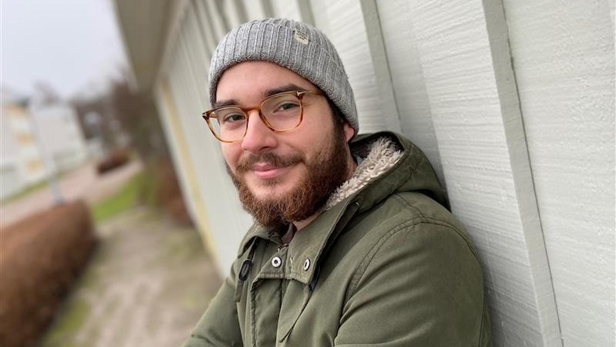 En man med grå mössa och glasögon lutar sej mot en vit vägg.