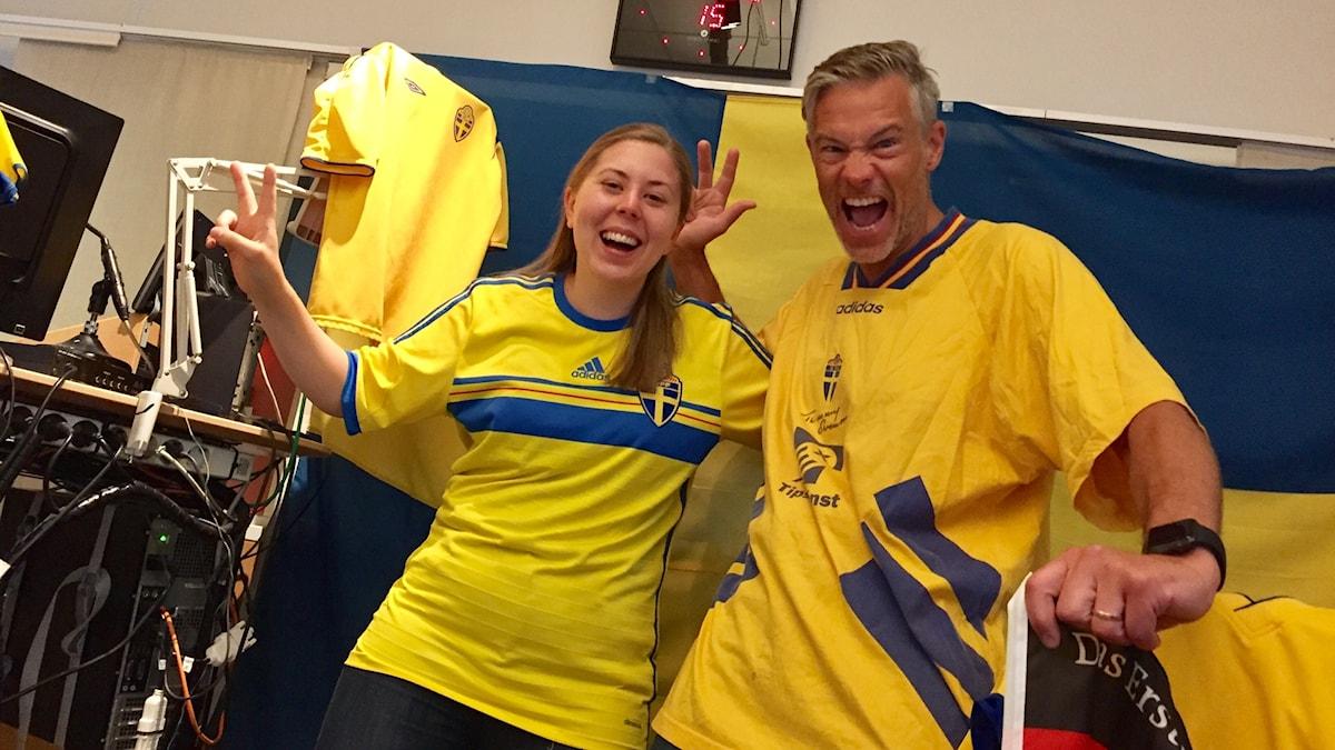 Anneli och Fredrik står i studion med sveroge tröjor och sverigeflaggor.