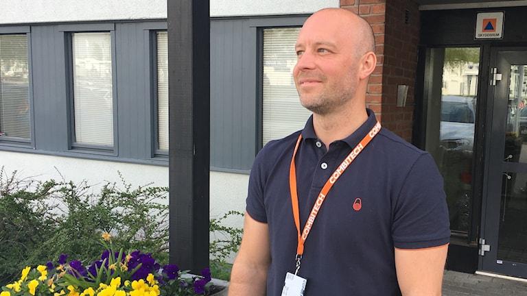 Jonas Stewén står utanför en dörr och tittar till vänster i bild.