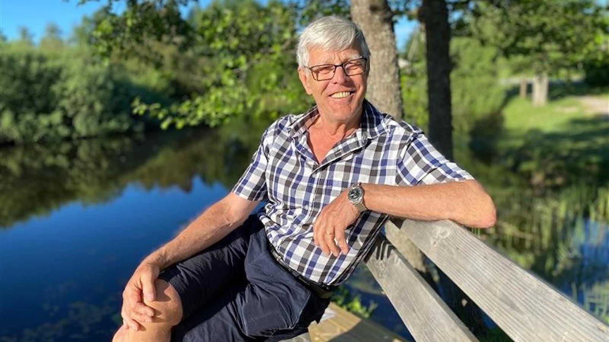 En man sitter på en bänk framför en stilla insjö en solig sommarmorgon.