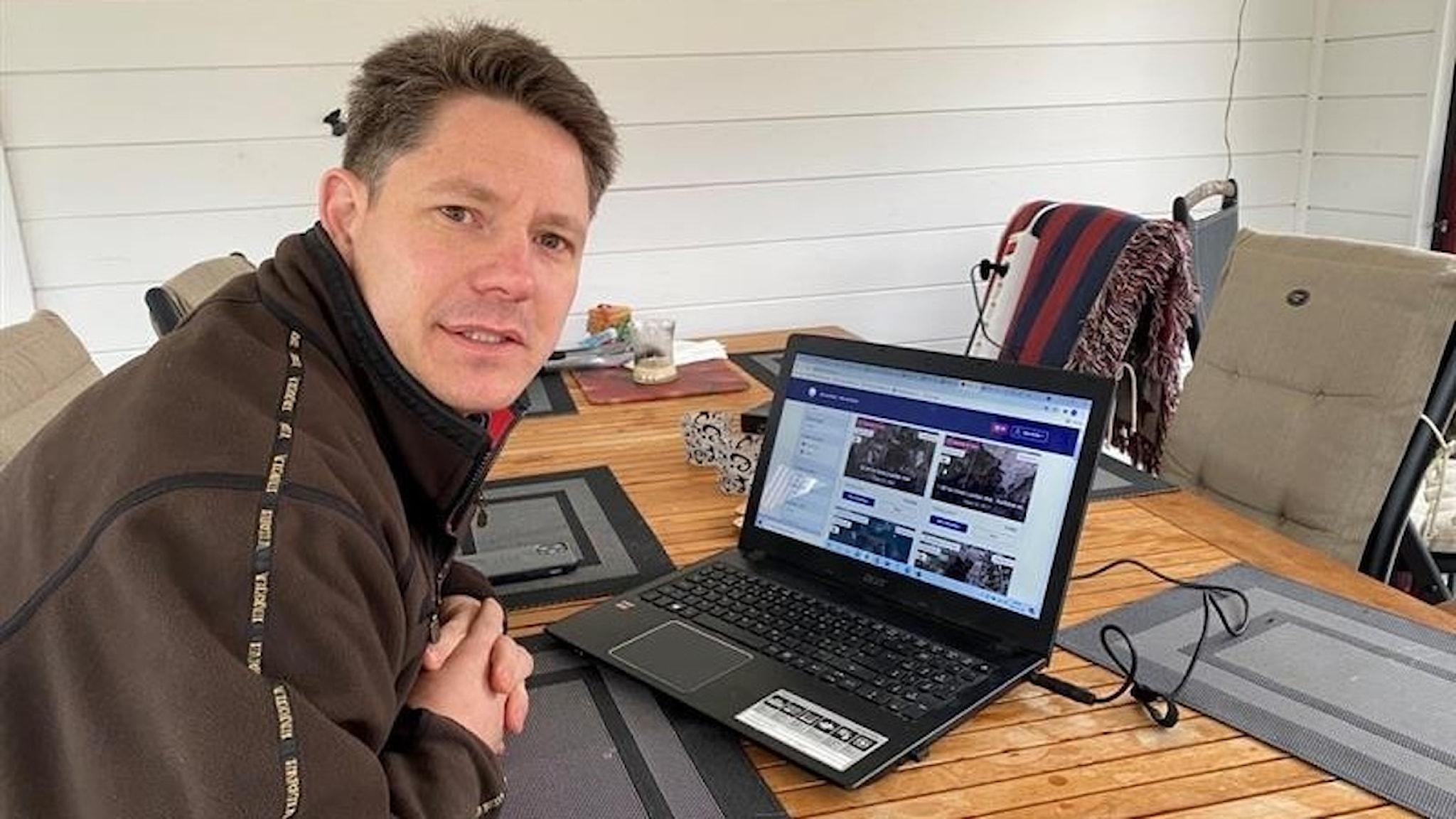 En man sitter vid en dator och tittar in i kameran.
