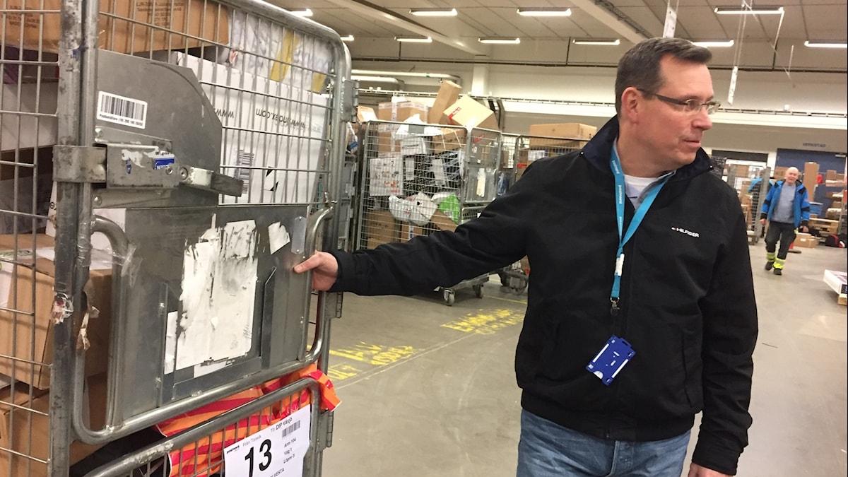 Robert Andersson står vid en vagn full med paket.