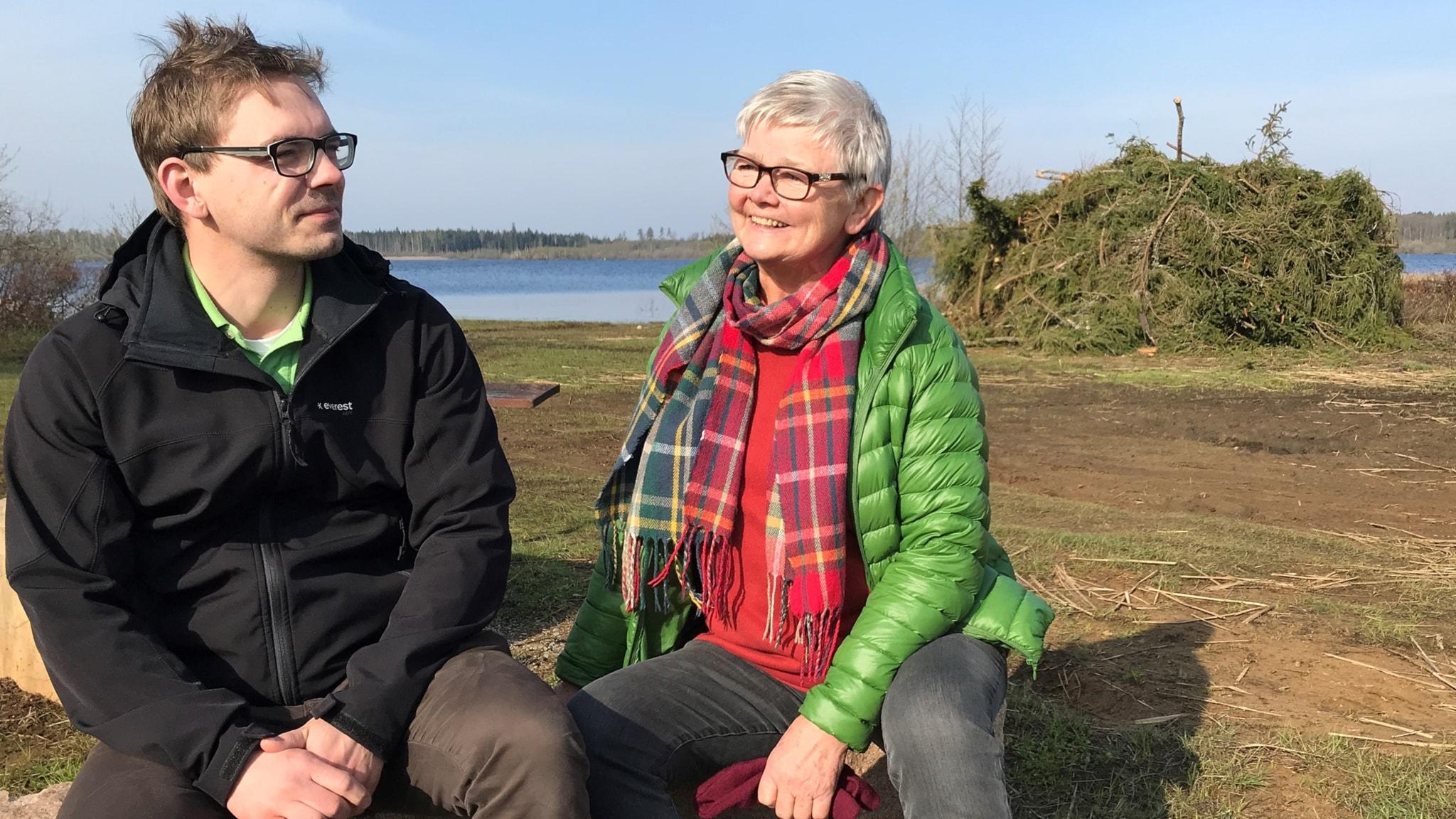 Jakob Sträng och Gunnel Förander sitter på en bänk framför riset som ska tändas till majbrasan, man ser också sjön i bakgrunden.