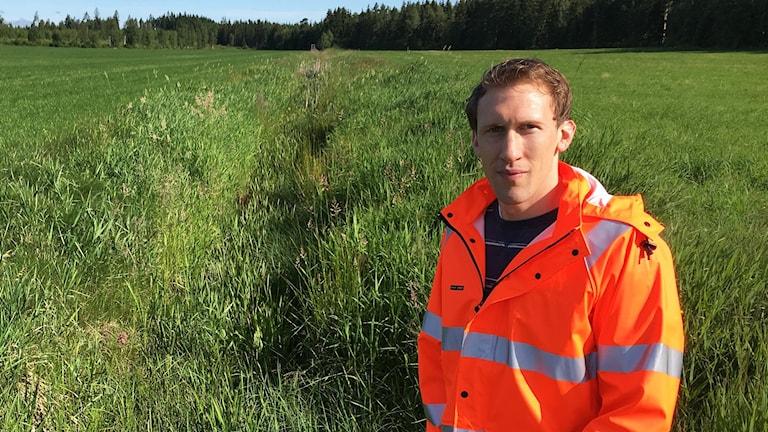 En man i orange jacka står vid en bäck med massa gräs och vass i.