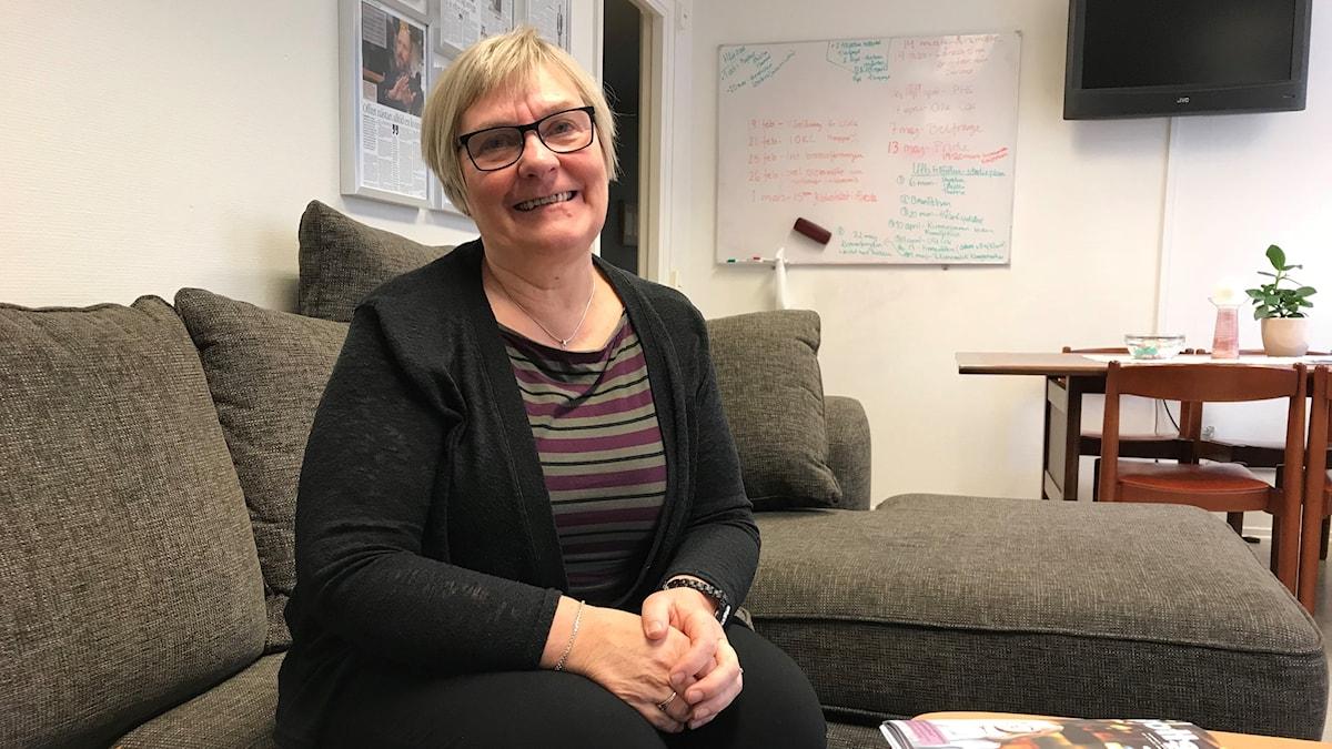 Marie-Louise Gustavsson är ordförande i Brottsofferjouren Växjö och sitter i en grå soffa.