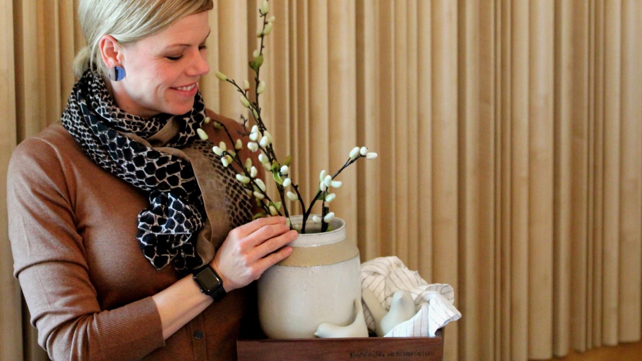 Erika Johansson håller i en träbricka med prydnadsfåglar, en linneduk och en keramikvas med videkvistar på.