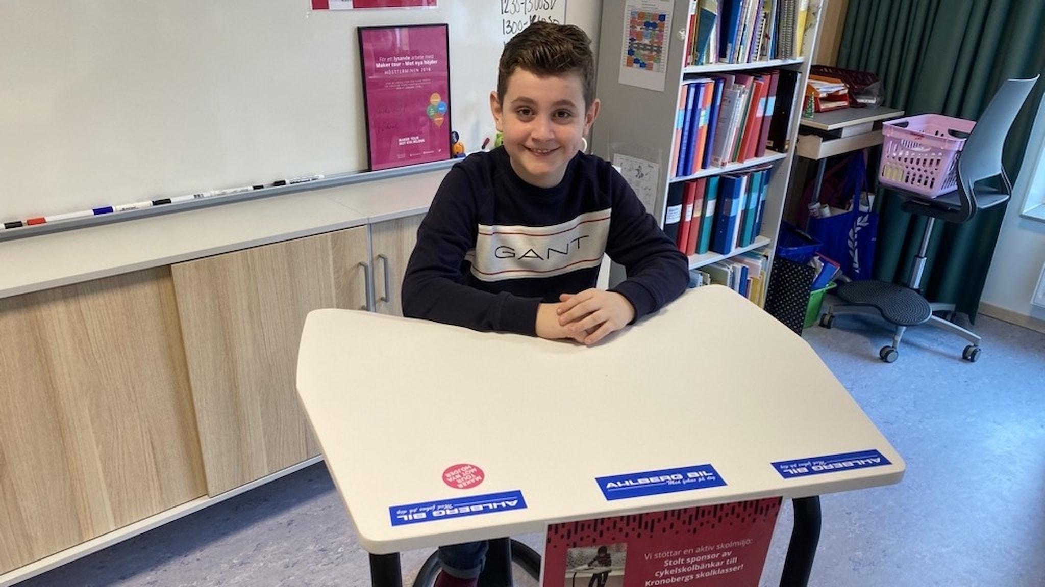 Harun Duzel, elev på Hjortsbergskolan i Ljungby, sitter vid en cykelskolbänk i ett klassrum.