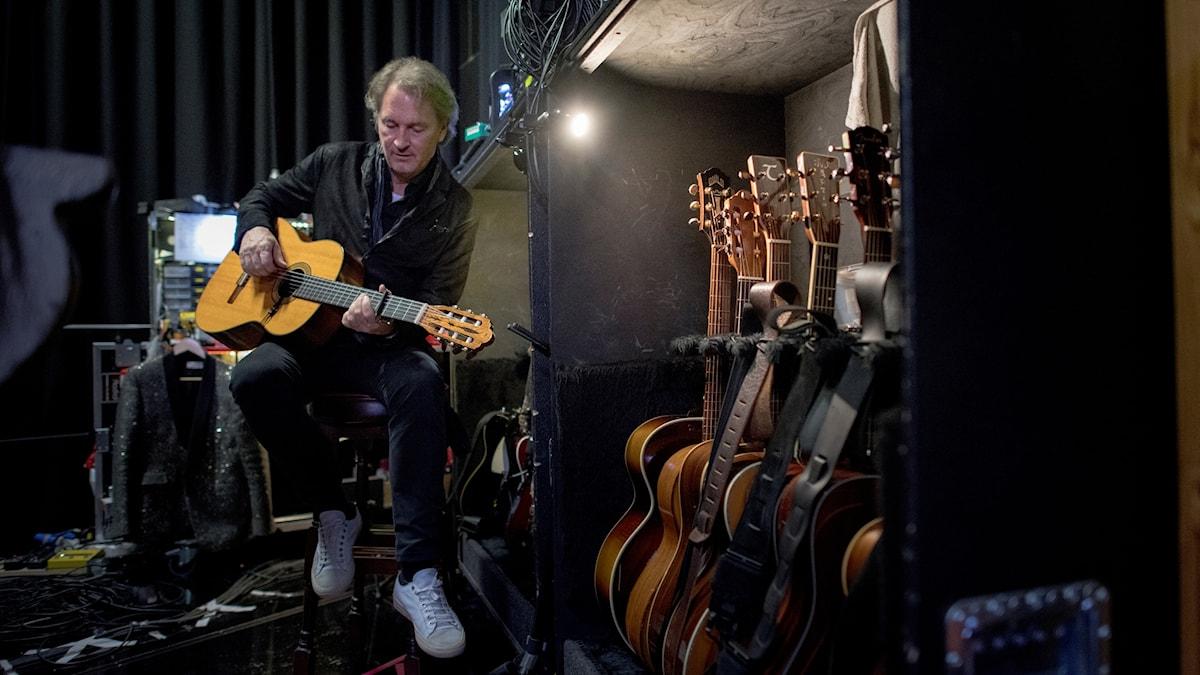 Tomas Ledin sitter på en pall och spelar gitarr.