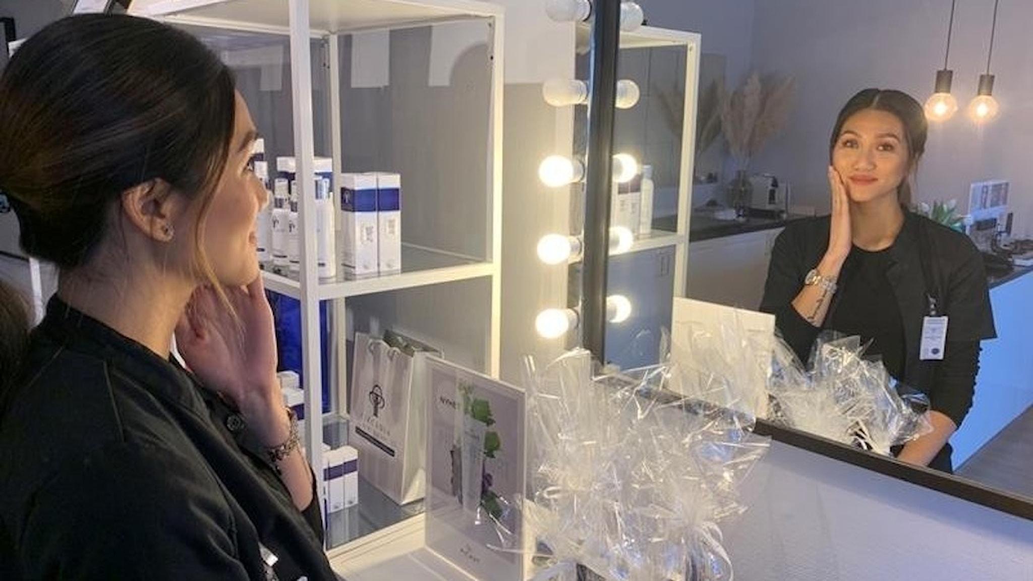 En kvinna står framför en spegel och smeker kinden.