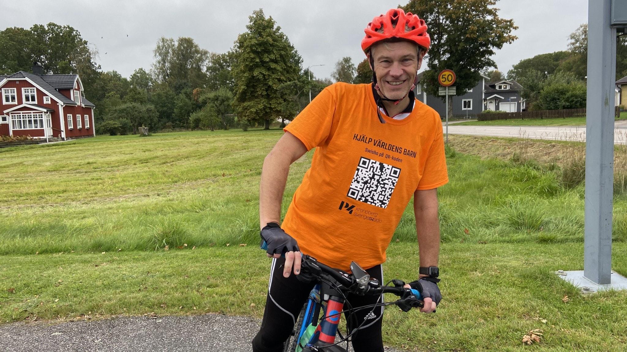 Fredrik B Ekdahl cyklar genom länet under Världens Barn-insamlingen. Han sitter på cykeln och har på sig en orange tröja med information om hur man skänker pengar till insamlingen.