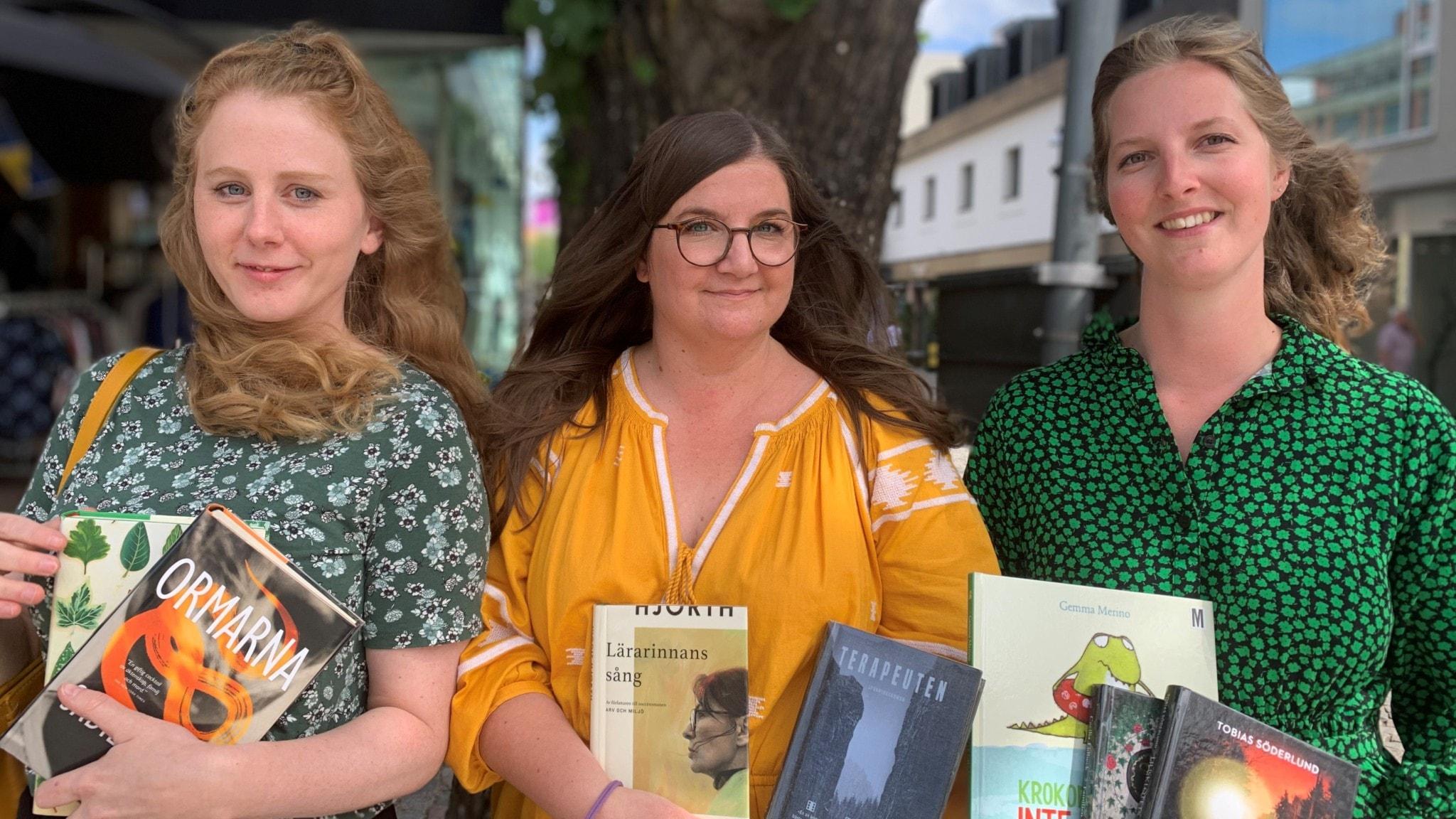 Tre bibliotekarier som håller i böcker