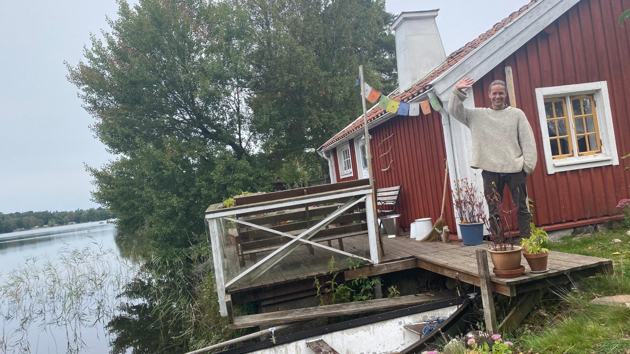 Pa Sandberg bor halvtid på en ö i Helgasjön. Här står han vinkandes på en brygga med sitt röda torp i bakgrunden. Bredvid honom är en liten båt i sjön.