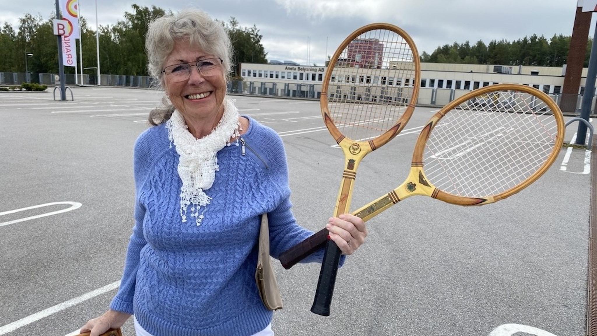 Lisbet Dahlin från Liatorp med gamla tennisracketar från 1950-talet. Hon håller i två stycken i sin ena hand.