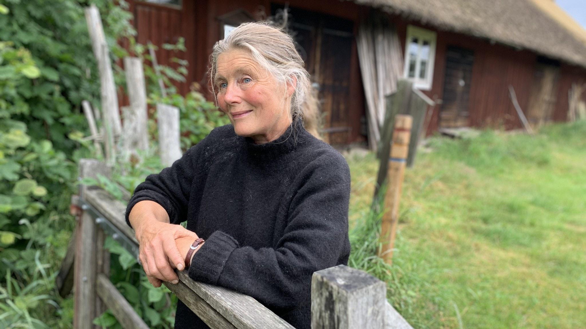 En gråhårig kvinna står lutad mot ett staket