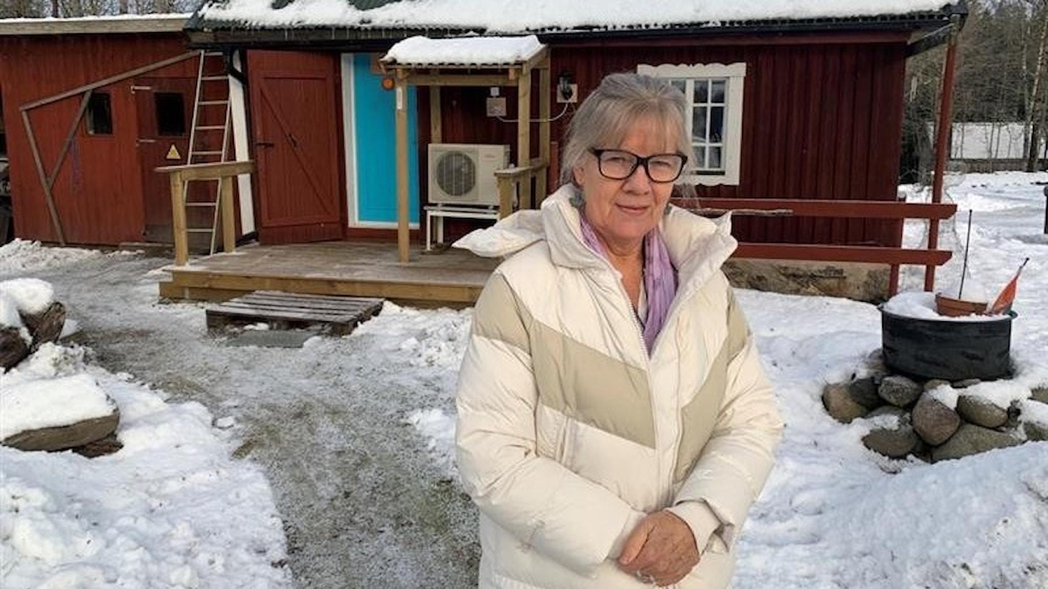 En kvinna står med en vit vinterkappa framför ett rött hus.