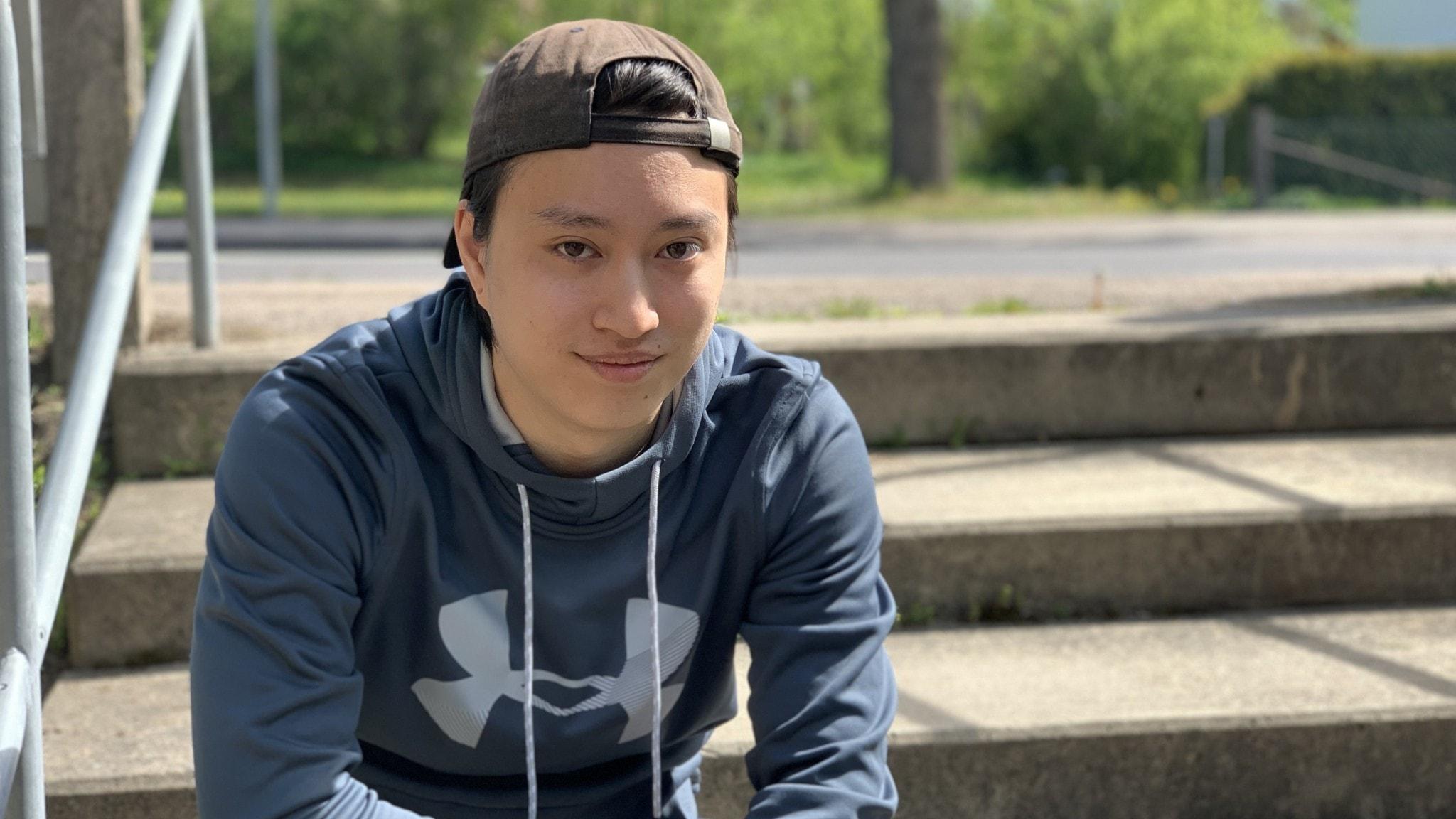 En kille sitter på en trappa iklädd blå hoodie och keps.
