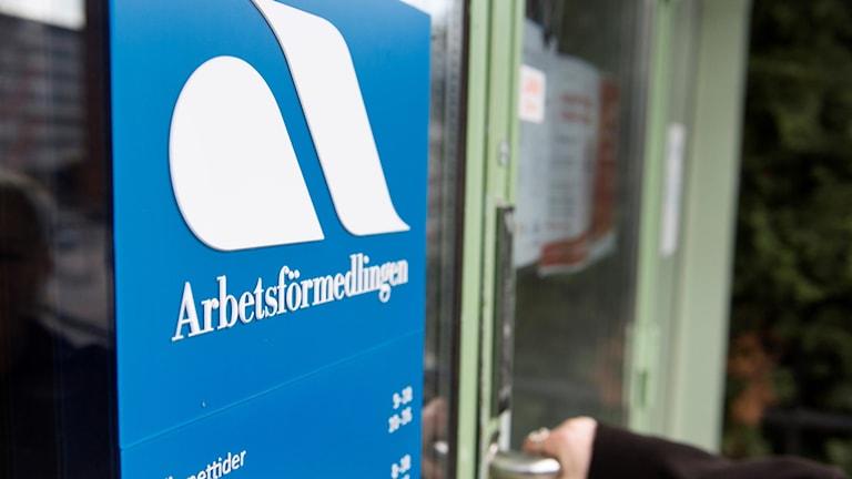 En blå skylt som tillhör arbetsförmedlingen och en hand som öppnar en dörr