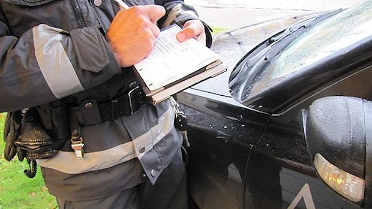 Parkeringsvakt skriver en parkeringsbot. Foto: Camilla Olsson/SR Västmanland.