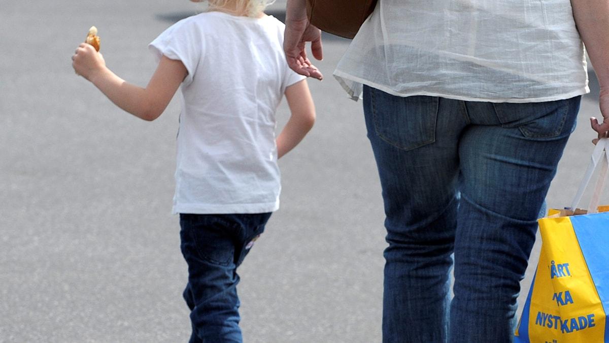 En mamma med en papperskasse full med varor och dottern springer framför henne.