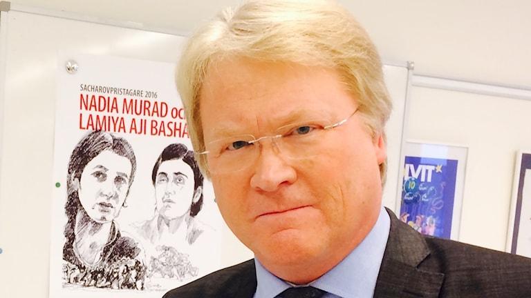 Lars Adaktusson framför affischen med Nadia Murad och Limaya Aji Bashar