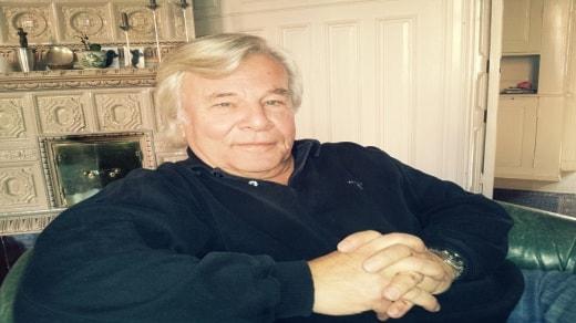 Jan Gouilleou sitter hemma i fåtölj. Foto: Besir Kavak, Sveriges Radio