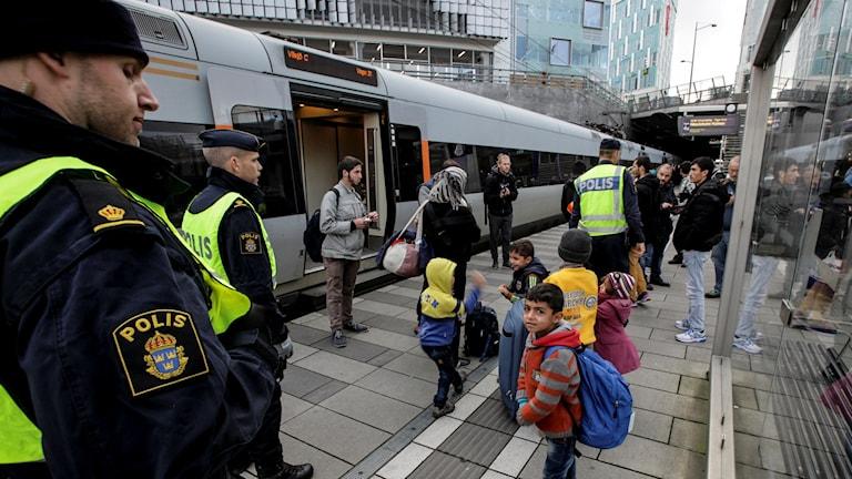 Poliser och flyktingar som står på tågstation. Foto: TT