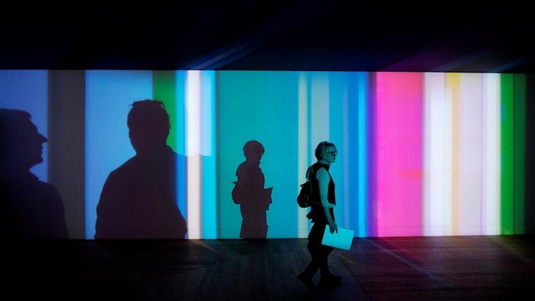 Människor och skuggor belysta i olika färger i en utställningshall på Moderna museet. Foto: Vilhelm Stokstad/TT.